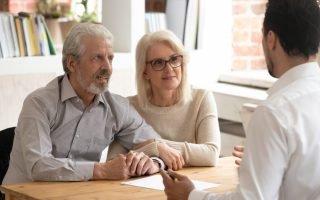 casal de idosos conversa com corretor sobre vender imóvel