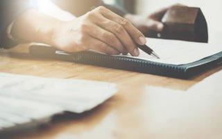 mão masculina assina contrato para financiar um apartamento