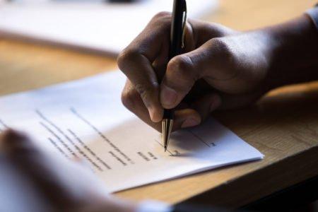 mão masculina assina contrato de consórcio