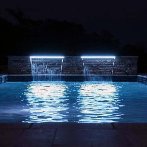 cascata iluminada sobre a piscina