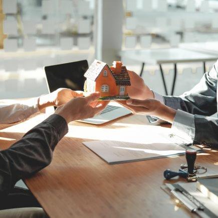 corretor de imóveis segura casa em miniatura para casal de compradores